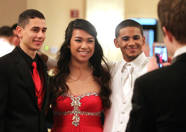 Salem juniors Gabriel Andreottola, Cathy Nguyen, and Jimaldy Baez pose for a photo being taken by classmate Emmanuel Silva Marte, right, at Salem High School's junior prom held at the Peabody Marriott Hotel on Friday evening. DAVID LE/Staff photo 4/4/14