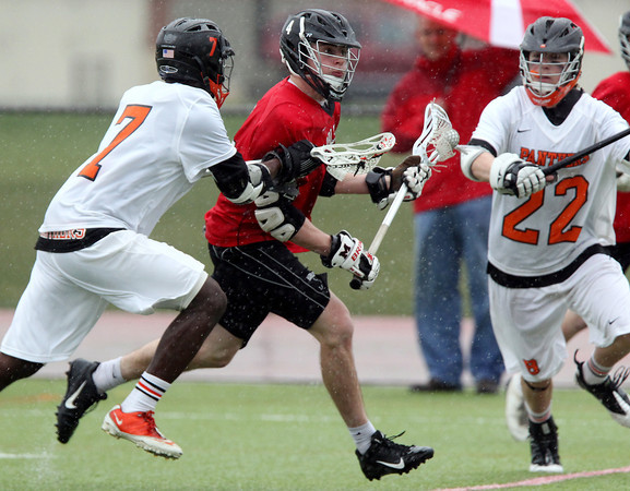 Marblehead junior midfielder Brooks Tyrrell (4) splits Beverly sophomore midfielder Peter Mulumba (7) and senior defense Dylan Jutras (22) while carrying the ball upfield on Tuesday afternoon. DAVID LE/Staff photo 4/15/14