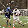 KEN YUSZKUS/Staff photo.  Danvers' Mike Favreau charges Marblehead's Harrison Young during the Danvers at Marblehead boys lacrosse game. 4/23/14