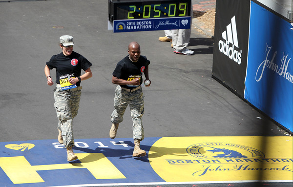 Two members of the National Guard cross the finish line to a standing ovation and loud cheers from thousands at the finish line of the 118th Boston Marathon on Monday morning. DAVID LE/Staff photo 4/21/14