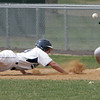 KEN YUSZKUS/Staff photo. Danvers' Chris Valles slides back safely to 1st base with Marblehead's Tom Koopman eyeing the incoming ball during the Marblehead at Danvers baseball game.