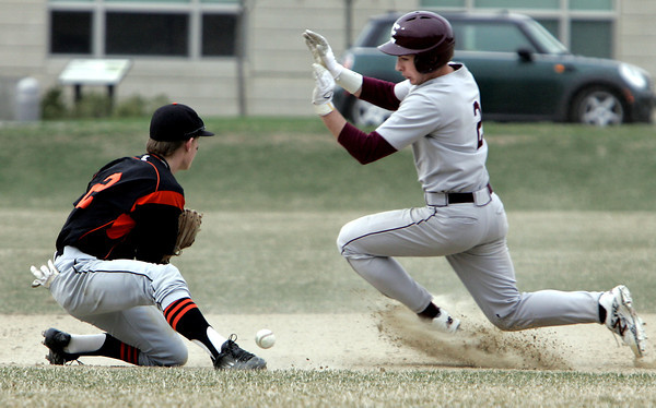 KEN YUSZKUS/Staff photo. Beverly's Sean Curtin can not get a handle on the ball to stop the Lynn English 2 player from safely getting to 2nd safe on a steal at the Lynn English at Beverly High School baseball game.