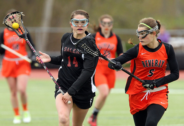 Salem midfielder Alexa Gilbert (14) carries the ball upfield while being chased down by Beverly midfielder Grace Otterbein (5) during the first half of play on Wednesday afternoon. DAVID LE/Staff photo. 4/30/14