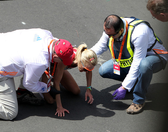 Marblehead native Shalane Flanagan gets assistance from medical personnel after she collapsed in exhaustion after crossing the finish line of the 118th Boston Marathon. Flanagan ran a personal best time of 2:22:02, good for 7th place overall in the Women's Elite race on Monday morning. DAVID LE/Staff photo 4/21/14