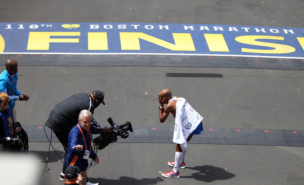 Meb Keflezighi, the 118th Boston Marathon Men's Elite champion holds his face in his hands in disbelief just across the finish line after he took home the title in a time of 2:08:37 on Monday morning. DAVID LE/Staff photo 4/21/14