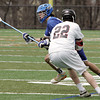 KEN YUSZKUS/Staff photo.  Danvers' Anthony Serino runs the ball around Marblehead's Harrison Young during the Danvers at Marblehead boys lacrosse game. 4/23/14