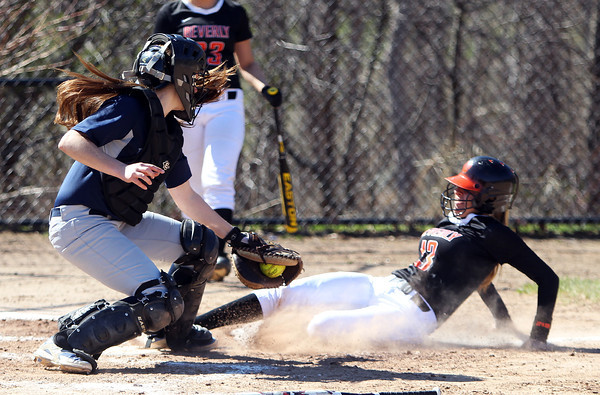 Beverly senior Kate Silvestri (13) slides in safely at home plate ahead of the tag from Swampscott catcher Olivia Cooke (5). Silvestri scored one of the Panthers three runs in the top of the 7th, however, the Big Blue rallied from three-runs down in the bottom of the 7th inn in for a 10-9 walk off win over the Panthers in NEC action on Thursday afternoon. DAVID LE/Staff photo. 4/24/14