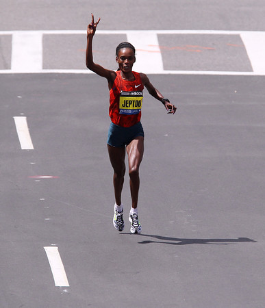 Kenyan Rita Jeptoo holds up two fingers to signify two Boston Marathon wins in a row as she sprints the final quarter mile to the finish line of the 118th Boston Marathon on Monday afternoon. DAVID LE/Staff photo 4/21/14