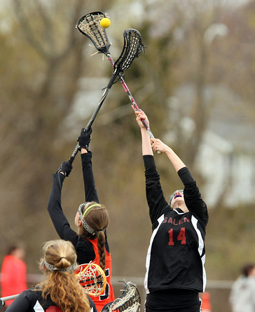 Salem midfielder Alexa Gilbert (14) and Beverly midfielder Grace Otterbein (5) leap high in the air and battle for a face-off win during the first half of play on Wednesday afternoon. DAVID LE/Staff photo. 4/30/14