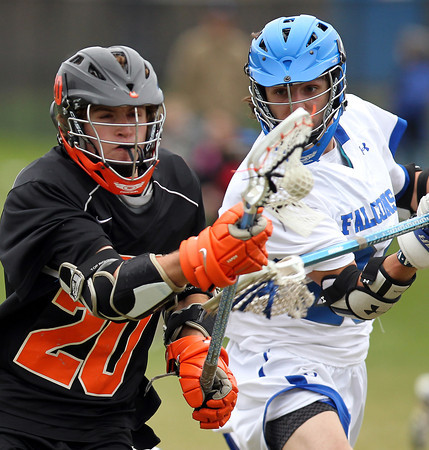 Beverly midfielder Elias Crandell (20) tries to keep hold of the ball while being stick checked by Danvers defense Anthony Serino (20) on Monday afternoon. DAVID LE/Staff Photo. 4/28/14