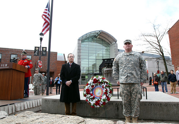 Lt. Col Shawn Cody, of the 101st Engineer Battalion, right, and Jay Finney, Chief Marketing Officer of the Peabody Essex Museum stand at attention after placing a wreath to remember Essex County men who were killed during the Battles of Lexington and Concord as Lt. Col. Larry Conway, Commander of the Second Corps Cadets Veterans Association of Salem, left, speaks during a ceremony at Armory Park as part of the 377th Anniversary of the First Muster on Salem Common. DAVID LE/Staff photo 4/5/14