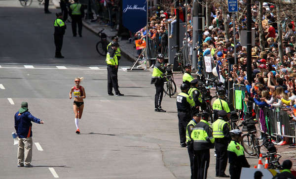Marblehead native Shalane Flanagan gets loud cheers from thousands of people packed along the Boylston Street home straightaway as she finishes in 7th place in the 118th running of the Boston Marathon on Monday morning. DAVID LE/Staff photo 4/20/14