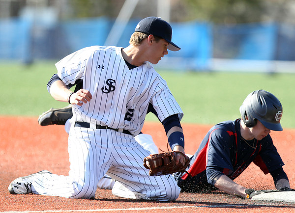 St. John's Prep first baseman Sawyer Billings (12) swipes the tag towards Central Catholic's Kevin Regan as he slides back into first base on a pickoff attempt. The Eagles cruised to a 9-3 win over the Raiders at St. John's Prep in Danvers on Thursday afternoon. DAVID LE/Staff photo 4/10/14
