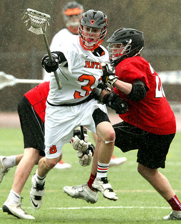 Beverly junior defense Bryan Flaherty (33) manages to evade Marblehead defense Ryan Jones, right, and carry the ball into the Beverly attacking zone on Tuesday afternoon. DAVID LE/Staff photo 4/15/14