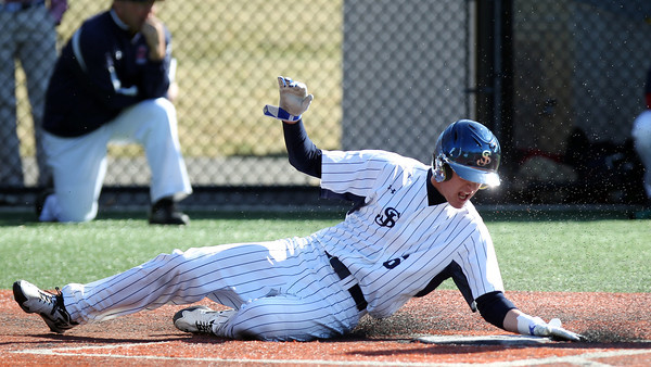 St. John's Prep senior captain Max Burt slides safely across home plate to score one of the Eagles 9-runs against Central Catholic. The Eagles cruised to a 9-3 win over the Raiders at St. John's Prep in Danvers on Thursday afternoon. DAVID LE/Staff photo 4/10/14