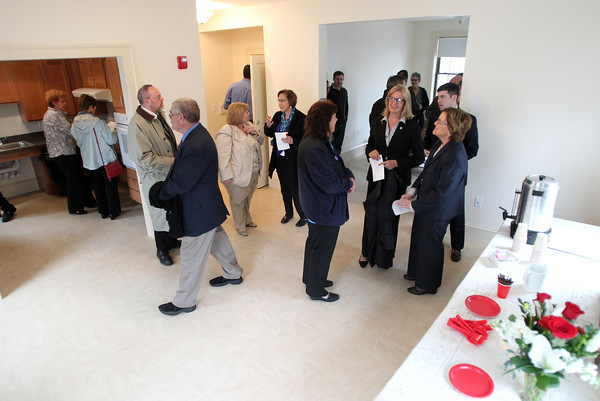 People mill through the kitchen and dining rooms of the affordable housing unit located at 24 Cherry Street in Danvers following a dedication ceremony on Wednesday morning. DAVID LE/Staff photo. 4/30/14