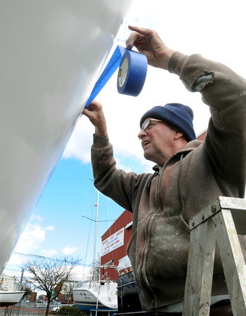 KEN YUSZKUS/Staff photo. Doug Bayliss of Ashburnham, tapes the stripe on his 40 foot sailboat before giving the hull a coat of white paint while it sits on stilts in Beverly.