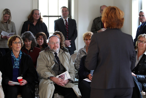People attending the dedication of the affordable housing unit at 24 Cherry Street in Danvers listen to Cynthia Dunn, Executive Director of the Danvers Housing Authority during the ceremony on Wednesday morning. DAVID LE/Staff photo. 4/30/14
