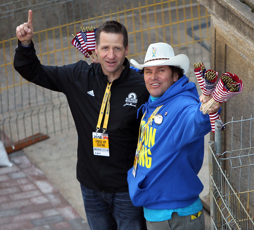 Carlos Arrendondo, right, one of the many heroes from the Boston Marathon bombings from last year, was handing out American flags and taking pictures near the finish line of the 118th Boston Marathon on Monday morning. DAVID LE/Staff photo 4/21/14