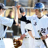 St. John's Prep junior Keith Leavitt (22) smiles as he is greeted coming back to the dugout by teammate Jacob Yish (27) after Leavitt scored the Prep's third run of the afternoon. The Eagles cruised to a 9-3 win over the Raiders at St. John's Prep in Danvers on Thursday afternoon. DAVID LE/Staff photo 4/10/14