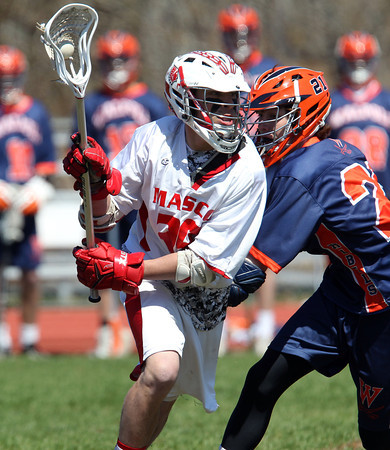 Masco senior midfielder Harry Cwik (28) spins away from Walpole sophomore midfielder Christopher O'Connell (21) during the second game of the Creator's Cup held at Masconomet Regional High School in Topsfield on Thursday afternoon. DAVID LE/Staff photo. 4/24/14
