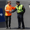 Bill Rodgers, a three-time winner of the Boston Marathon, shakes hands with a Boston police officer as he is introduced and jogs down to the finish line during the 118th running of the Boston Marathon. DAVID LE/Staff photo 4/21/14