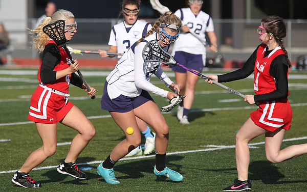 KEN YUSZKUS/Staff photo.   Peabody's Emma Rigol, middle, looses the ball with Salem's Hannah Gilrain, left, and Salem's Rebecca Cormier at her sides at the Salem at Peabody girls lacrosse game.       04/29/16