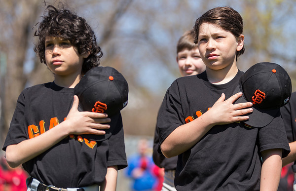 PARKER FISH/ photo. Sebastian Cruz (left) and Ramsey Pacheco (right) hold their hats over their hearts during the singing of the national anthem. 4/24/16