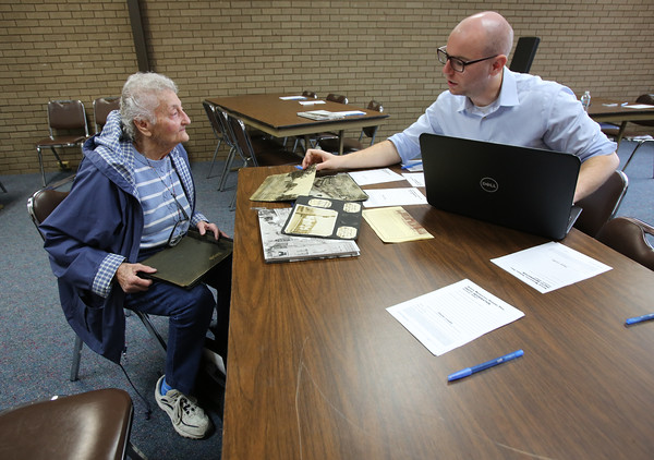 KEN YUSZKUS/Staff photo.     Fay Stearns of Salem, left, and Pediment acquisitions editor Jon Shields discuss the information for the photos she brought in to be scanned for the second volume of The Salem News' Salem Memories book.  04/19/16