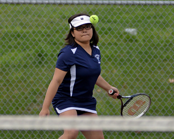 RYAN HUTTON/ Staff photo<br /> Peabody's Andeemae Sims eyes the ball speeding toward her during her 1st Doubles match with partner Chrisly Biqiku against Gloucester's Katie Nugent and Heidi Franke-Otten during Monday's tennis match at Peabody High.