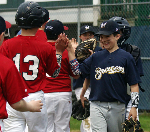 CASEY OLIVER/photo. Peabody West Little Leaguer Anthony Deamelio shares a laugh and slap high fives at the conclusion of the PWLL Jamboree on Friday Evening. 4/22/16.