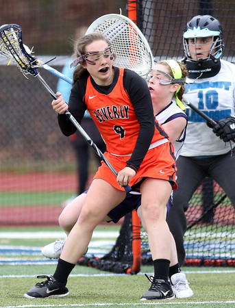 DAVID LE/Staff photo. Beverly's Melissa Laganas (9) backs down Peabody's Lauren Wolff and spins and fires a shot past Peabody goalie Gianna Denisco (10). 4/12/16.