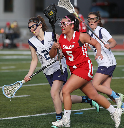 KEN YUSZKUS/Staff photo.   Salem's Brianna Valido, center, runs the ball down field with Peabody's Carla Patania at her side at the Salem at Peabody girls lacrosse game.       04/29/16