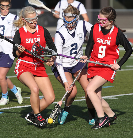 KEN YUSZKUS/Staff photo.   Peabody's Emma Rigol, middle, is squeezed by Salem's Hannah Gilrain, left, and Salem's Rebecca Cormier at the Salem at Peabody girls lacrosse game.       04/29/16