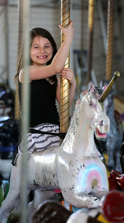 KEN YUSZKUS/Staff photo.    Malia Eagly of Salem rides a unicorn on the carousel at Salem Willows on a warm Friday afternoon.     04/21/16