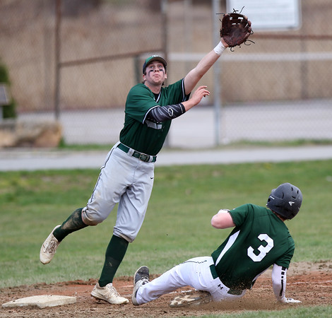 DAVID LE/Staff photo. Manchester-Essex's Chris Carr (3) slides into third base on a steal attempt as Pentucket third baseman Steve Noyes tries to leap and snag the throw. The ball soared past Noyes and Carr scored for the Hornets. 4/23/16.