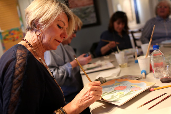 HADLEY GREEN/ Staff photo<br /> Sandra Willmer of Swampscott paints a serving dish at Paint and Sip Pottery Night with Patti DiCarlo Baker & Hestia Studios on April 14th, 2017.