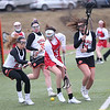 HADLEY GREEN/ Staff photo<br /> Masco's Maddie Casey (3) picks up the ball while surrounded by Beverly's Maeve Blake (21), Brooke Baeckey (30) and Darcey McAuliffe (16) during the Masco v. Beverly girls varsity lacrosse game at Beverly High on Friday, April 7th, 2017.