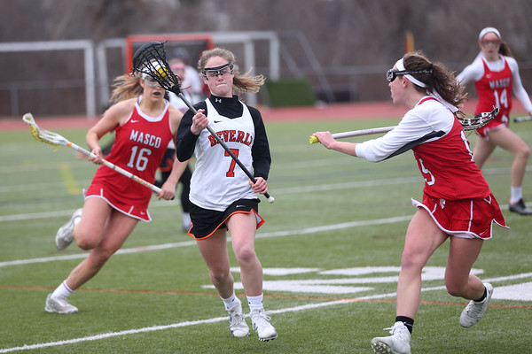 HADLEY GREEN/ Staff photo<br /> Beverly's Meg Cotraro (7) drives up the field while Masco's Grace Fahey (16) and Jordyn Tveter (15) guard her during the Masco v. Beverly girls varsity lacrosse game at Beverly High on Friday, April 7th, 2017.
