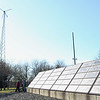 HADLEY GREEN/ Staff photo<br /> People walk by a windmill and solar panels at the  Greenergy Park Solar Field.