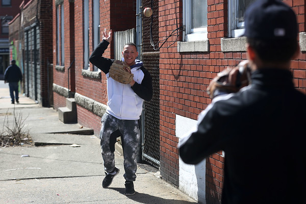 HADLEY GREEN/ Staff photo<br /> Kevin Rosario of Lynn and Jonathan Baez of Salem play catch outside the Ward Street basketball court in Salem on April 13th, 2017.