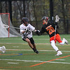 HADLEY GREEN/ Staff photo<br /> Beverly's Matt Rawding (20) runs up the field while Marblehead's Joe Moran (25) plays defense at the Marblehead v. Beverly boys varsity lacrosse game held at Marblehead High School on Tuesday, April 25th, 2017.