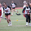 HADLEY GREEN/ Staff photo<br /> Masco's Tara Gallagher (12) and Beverly's Maeve Blake (21) and Darcey McAuliffe (16) vie for the ball during the Masco v. Beverly girls varsity lacrosse game at Beverly High on Friday, April 7th, 2017.