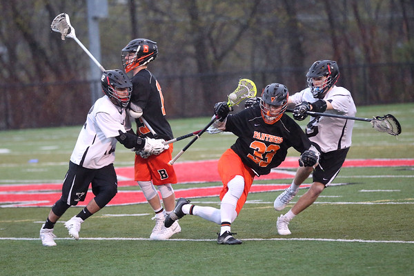 HADLEY GREEN/ Staff photo<br /> Beverly's Kevin Flaherty (33) keeps control of the ball while Marblehead's Paul Heffernan (6) plays defense at the Marblehead v. Beverly boys varsity lacrosse game held at Marblehead High School on Tuesday, April 25th, 2017.