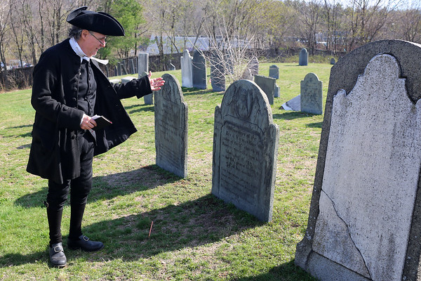 HADLEY GREEN/ Staff photo<br /> Reverend Bert White, chaplain of the Danvers Alarm List Company, motions to the grave of Reverend Nathan Holt, who he was reenacting, at the Old South Burial Ground in Salem. The Danvers Alarm List Company took part in a series of reenactments to commemorate fallen soldiers on Patriots Day.
