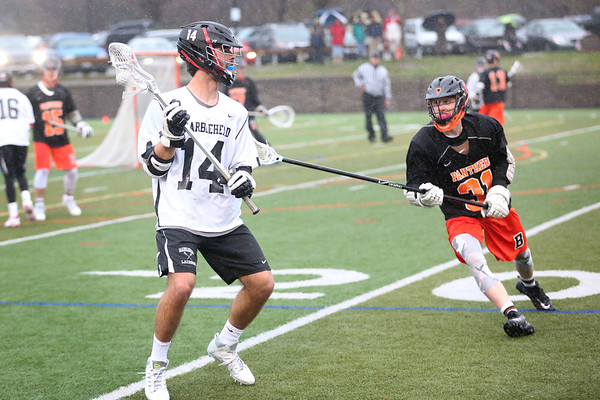 HADLEY GREEN/ Staff photo<br /> Marblehead's Sam Paquette (14) looks to pass the ball while Beverly's Johnny Jones (31) plays defense at the Marblehead v. Beverly boys varsity lacrosse game held at Marblehead High School on Tuesday, April 25th, 2017.