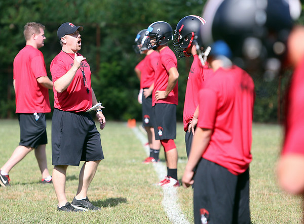 New Salem High School football head coach Matt Bouchard shouts instructions to his team during warmups on Monday afternoon. DAVID LE/Staff photo. 8/18/14.