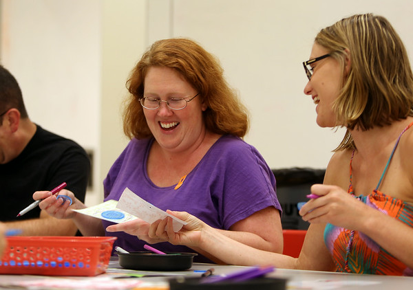 Heather Lang, left, and Holly DeHaan, both of Salem, smile as they compare their Spirograph Art during PEM PM at the Peabody Essex Museum's Throwback Game Night on Thursday evening. DAVID LE/Staff photo. 8/21/14.