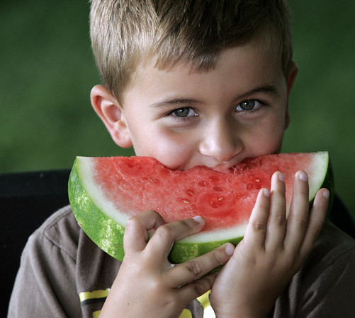 KEN YUSZKUS/Staff photo. Alex Ewaschuk, 6, bites into a large slice of watermelon at the Beverly Homecoming Lobster Festival.  8/6/14