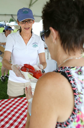 KEN YUSZKUS/Staff photo. Lori Reinhart serves up a lobster at the Beverly Homecoming Lobster Festival.  8/6/14
